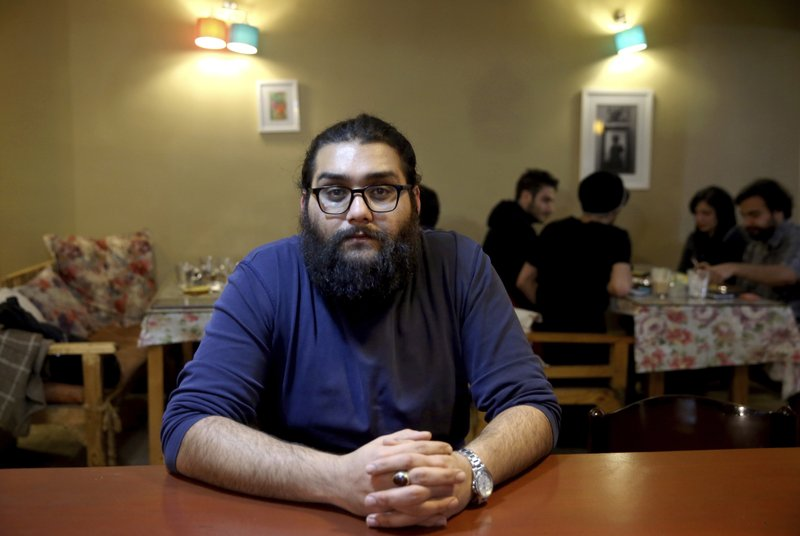 In this Tuesday, Jan. 29, 2019 photo, Ali Ghorbankhani, a 30-year-old artist and cafe waiter, is interviewed by The Associated Press about Iran's 1979 Islamic Revolution, in a cafe in downtown Tehran, Iran. (AP Photo/Ebrahim Noroozi)