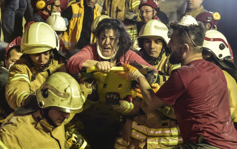 A woman reacts after rescue workers had pulled her out the rubble of an eight-story building which collapsed in Istanbul, Wednesday, Feb. (DHA via AP)