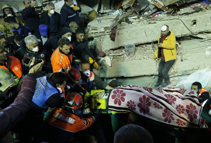 Rescue workers carry a woman from the rubble of an eight-story building which collapsed in Istanbul, Wednesday, Feb. (AP Photo/ Emrah Gurel)