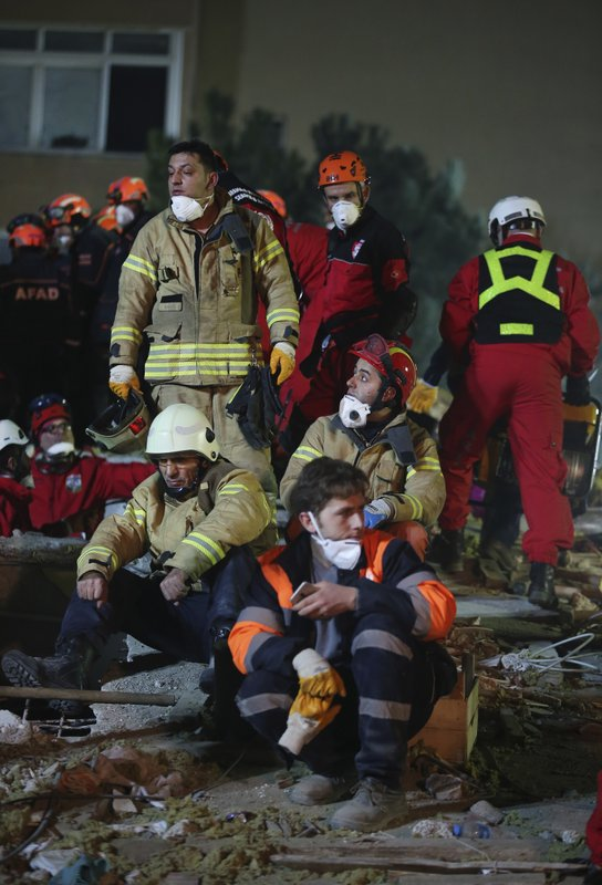 Rescue workers take a break from searching for survivors at the rubble of an eight-story building which collapsed in Istanbul, late Wednesday, Feb. (AP Photo/ Emrah Gurel)
