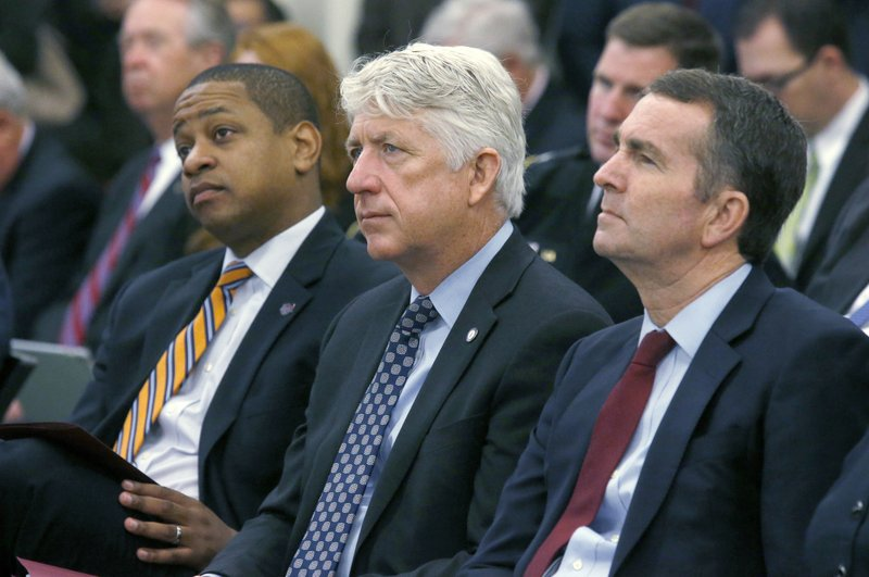 FILE - In this Dec. 18, 2017 file photo, from left, Lt. Governor-elect Justin Fairfax, Attorney General-elect Mark Herring and Governor-elect Ralph Northam listen as Virginia Governor Terry McAuliffe addresses a joint meeting of the House and Senate money committees at the Pocahontas Building in Richmond, Va. (Bob Brown/Richmond Times-Dispatch via AP)