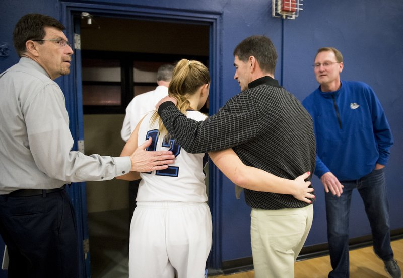 In this Feb. 13, 2015, photo, Gonzaga Prep assistant coach John Stockton walks arm-in-arm with his daughter Laura Stockton (12) after her team won the district championship against Central Valley, in Spokane, Wash. (Colin Mulvany/The Spokesman-Review via AP)