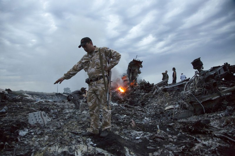FILE - In this July 17, 2014 file photo, people walk amongst the debris at the crash site of a passenger plane near the village of Grabovo, Ukraine. (AP Photo/Dmitry Lovetsky, File)