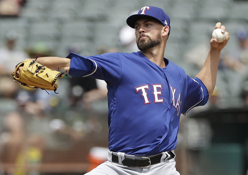 FILE - In this Aug. 22, 2018, file photo, Texas Rangers pitcher Mike Minor throws against the Oakland Athletics during the first inning of a baseball game, in Oakland, Calif. (AP Photo/Jeff Chiu, File)
