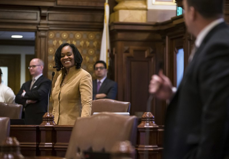 State Sen. Kimberly Lightford, D-Maywood, reacts as Sen. Michael Hastings, D-Tinley Park, praises her work on Senate Bill 1, a bill sponsored by Lightford to raise the state's minimum wage to $15 an hour by 2025, during debate on the Senate floor at the Illinois State Capitol, Thursday, Feb. (Justin L. Fowler/The State Journal-Register via AP)