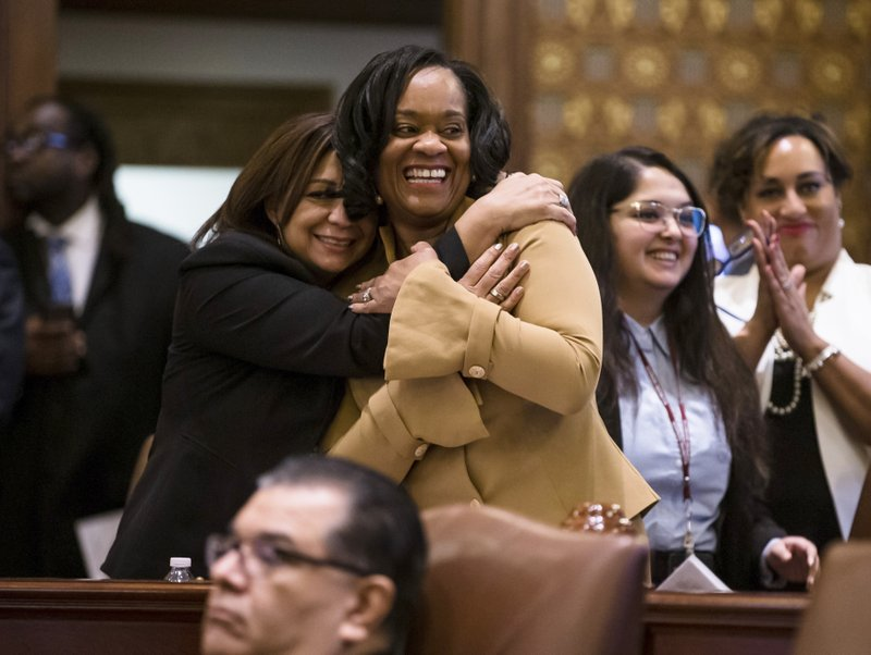 Illinois State Sen. Kimberly Lightford, D-Maywood, center, gets a hug from Illinois State Sen. Iris Martinez, D-Chicago, after Senate Bill 1, a bill sponsored by Lightford to raise the state's minimum wage to $15 an hour by 2025, passed the Senate on a vote of 39-18 at the Illinois state Capitol, Thursday, Feb. (Justin L. Fowler/The State Journal-Register via AP)