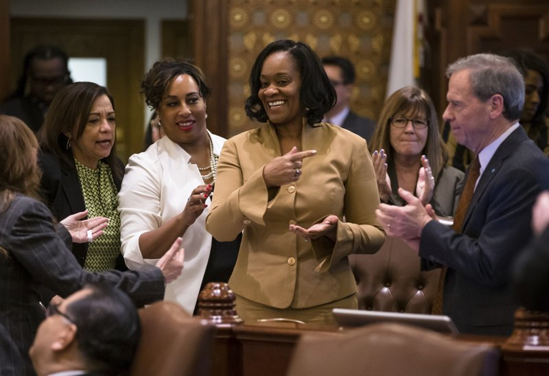 State Sen. Kimberly Lightford, D-Maywood, center, is applauded by Sens. Iris Martinez, D-Chicago, left, Toi Hutchinson, D-Olympia Fields, and Senate President John Cullerton, D-Chicago, right, after Senate Bill 1, a bill she sponsored to raise the state's minimum wage to $15 an hour by 2025, passed the Illinois Senate with a vote of 39-18 at the Illinois State Capitol, Thursday, Feb. (Justin L. Fowler/The State Journal-Register via AP)