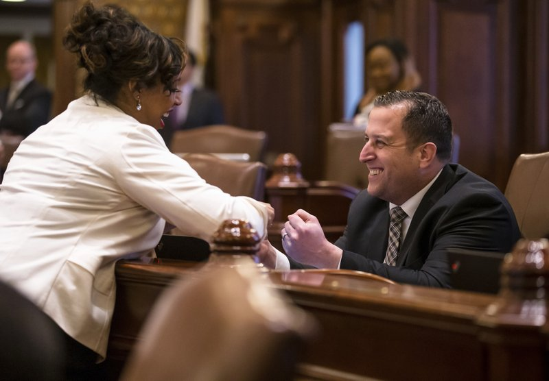 State Sen. Michael Hastings, D-Tinley Park, right, gets a fist bump from Sen. Toi Hutchinson, D-Chicago Heights, after delivering his remarks on Senate Bill 1, a bill to raise the state's minimum wage to $15 an hour by 2025, during debate on the Senate floor at the Illinois State Capitol, Thursday, Feb. (Justin L. Fowler/The State Journal-Register via AP)
