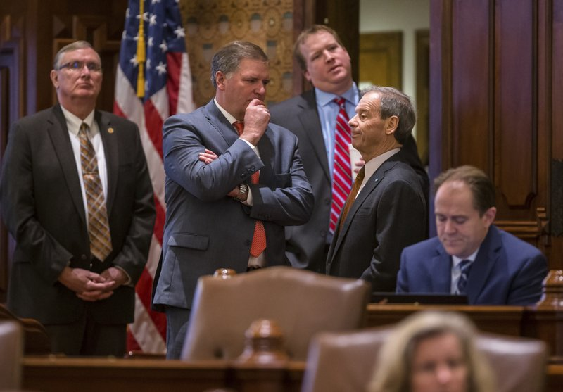 Illinois Senate Republican Leader Bill Brady, center, R-Bloomington, talks with Illinois Senate President John Cullerton, D-Chicago, right, during debate on on Senate Bill 1, a bill to raise the state's minimum wage to $15 an hour by 2025, on the Senate floor at the Illinois State Capitol, Thursday, Feb. (Justin L. Fowler/The State Journal-Register via AP)