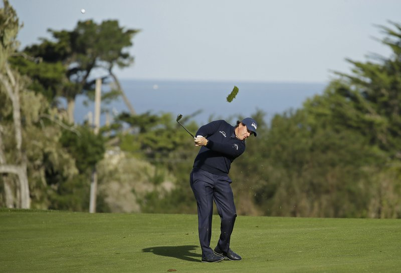 Phil Mickelson hits his approach shot from the second fairway of the Monterey Peninsula Country Club Shore Course during the first round of the AT&T Pebble Beach National Pro-Am golf tournament Thursday, Feb. (AP Photo/Eric Risberg)