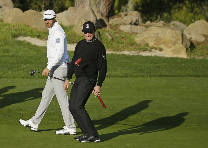 Wayne Gretzky, right, reacts after missing a putt as Dustin Johnson watches on the second green of the Monterey Peninsula Country Club Shore Course during the first round of the AT&T Pebble Beach National Pro-Am golf tournament Thursday, Feb. (AP Photo/Eric Risberg)