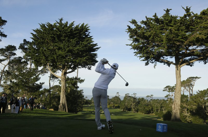 Dustin Johnson hits from the first tee of the Monterey Peninsula Country Club Shore Course during the first round of the AT&T Pebble Beach National Pro-Am golf tournament Thursday, Feb. (AP Photo/Eric Risberg)