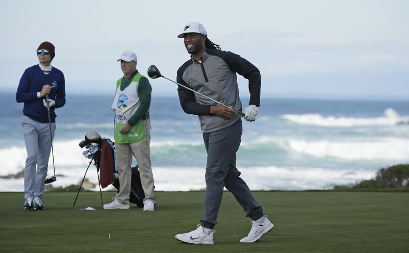 Larry Fitzgerald Jr., right, follows his drive from the 13th tee of the Monterey Peninsula Country Club Shore Course during the first round of the AT&T Pebble Beach National Pro-Am golf tournament Thursday, Feb. (AP Photo/Eric Risberg)