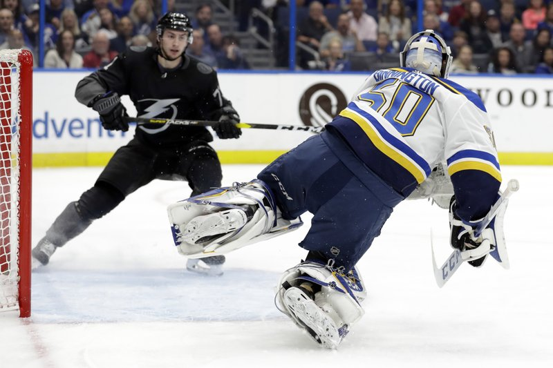St. Louis Blues goaltender Jordan Binnington (50) gets tripped up after making a save on a shot by Tampa Bay Lightning center Anthony Cirelli (71) during the second period of an NHL hockey game Thursday, Feb. (AP Photo/Chris O'Meara)