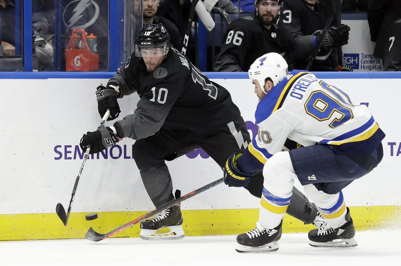 Tampa Bay Lightning center J.T. Miller (10) flips a pass by St. Louis Blues center Ryan O'Reilly (90) during the second period of an NHL hockey game Thursday, Feb. (AP Photo/Chris O'Meara)