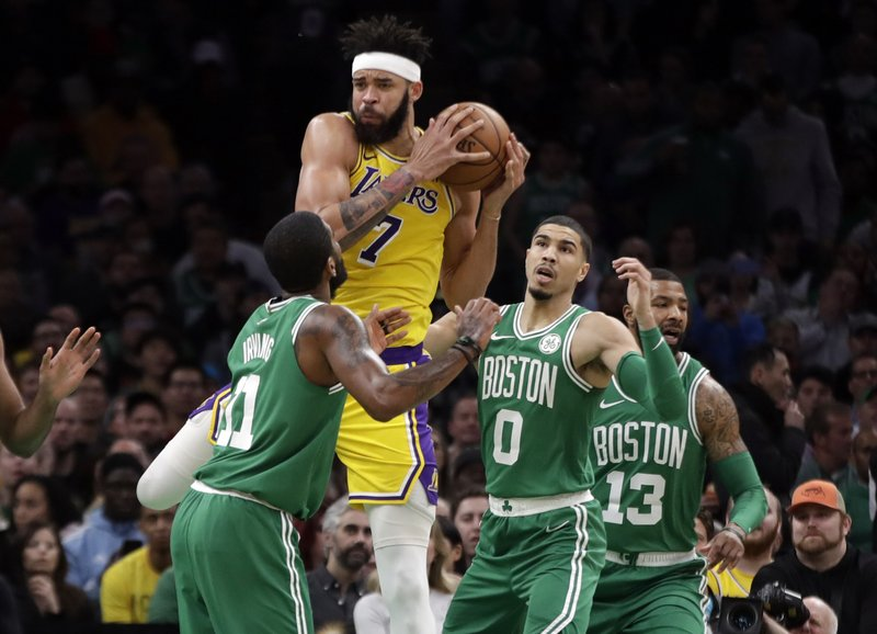 Los Angeles Lakers center JaVale McGee (7) grabs a rebound against Boston Celtics guard Kyrie Irving (11), forward Jayson Tatum (0) and forward Marcus Morris (13) in the first quarter of an NBA basketball game, Thursday, Feb. (AP Photo/Elise Amendola)
