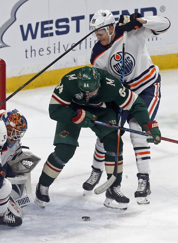 Edmonton Oilers' goalie Cam Talbot, lower left, looks on as Jesse Puljujarvi, right, of Sweden, defends against Minnesota Wild's Mikael Granlund of Finland during the first period of an NHL hockey game Thursday, Feb. (AP Photo/Jim Mone)