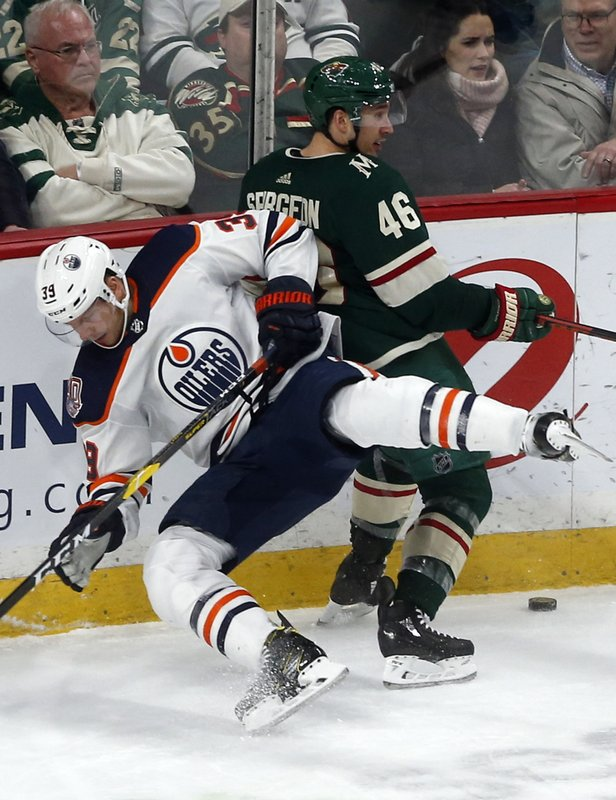 Edmonton Oilers' Alex Chiasson, left, falls as he and Minnesota Wild's Jared Spurgeon battle for the puck along the boards during the second period of an NHL hockey game Thursday, Feb. (AP Photo/Jim Mone)