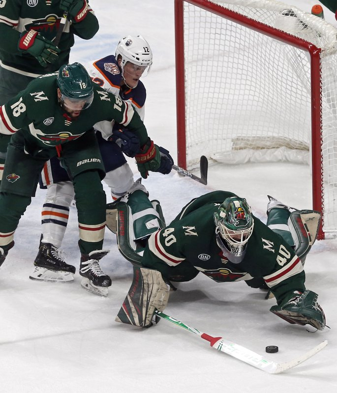 Minnesota Wild goalie Devan Dubnyk, right, dives for the puck as Jordan Greenway, left, keeps Edmonton Oilers' Colby Cave away during the first period of an NHL hockey game Thursday, Feb. (AP Photo/Jim Mone)