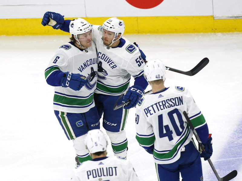 Vancouver Canucks defenseman Alex Biega (55) celebrates with right wing Brock Boeser (6) after his goal against the Chicago Blackhawks during the second period of an NHL hockey game Thursday, Feb. (AP Photo Nuccio DiNuzzo)