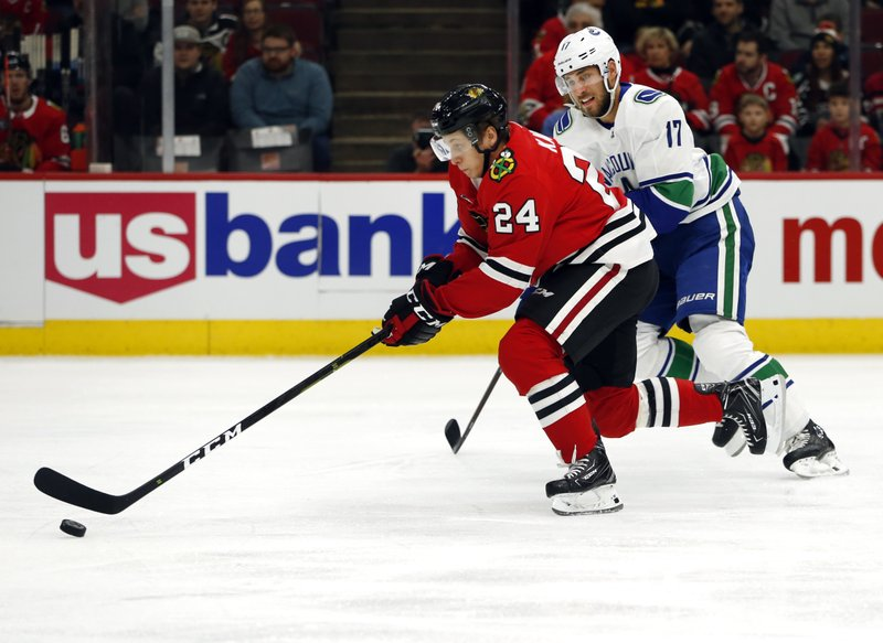 Chicago Blackhawks center Dominik Kahun (24) controls the puck away from Vancouver Canucks left wing Josh Leivo (17) during the first period of an NHL hockey game Thursday, Feb. (AP Photo Nuccio DiNuzzo)