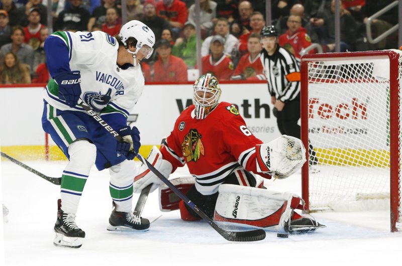 Chicago Blackhawks goaltender Collin Delia (60) stops a shot by Vancouver Canucks left wing Loui Eriksson (21) during the first period of an NHL hockey game Thursday, Feb. (AP Photo Nuccio DiNuzzo)