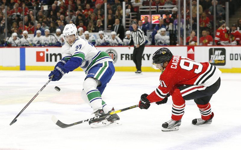 Vancouver Canucks defenseman Ben Hutton (27) and Chicago Blackhawks center Drake Caggiula (91) chase a loose puck during the first period of an NHL hockey game Thursday, Feb. (AP Photo Nuccio DiNuzzo)