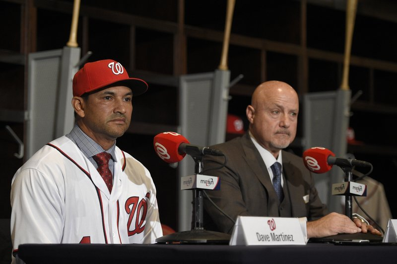 FILE - In this Nov. 2, 2017, file photo, Washington Nationals manager Dave Martinez, left, looks on next to general manager Mike Rizzo, right, as he speaks during a baseball news conference in Washington. (AP Photo/Nick Wass, File)