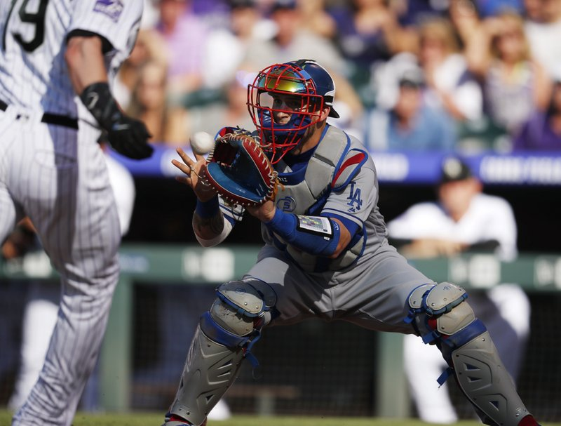 FILE - In this June 2, 2018, file photo, Los Angeles Dodgers catcher Yasmani Grandal fields the throw from left fielder Matt Kemp to put out Colorado Rockies' Charlie Blackmon during the first inning of a baseball game in Denver. (AP Photo/David Zalubowski, File)