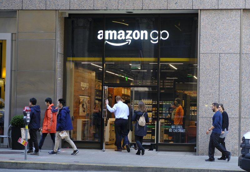 In this Wednesday, Jan. 30, 2019, photo people walk past and into an Amazon Go store in San Francisco. (AP Photo/Eric Risberg)