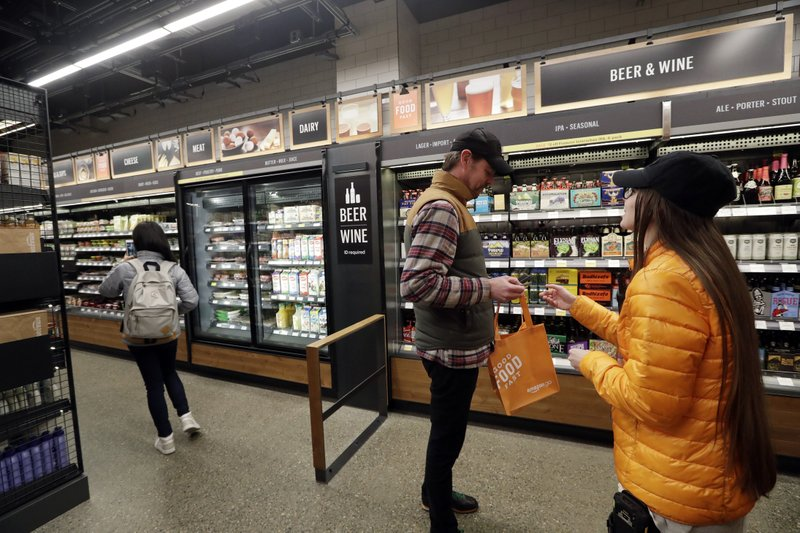 FILE- In this Jan. 22, 2018, file photo, a worker, right, looks at the ID of a shopper at the wine and beer area inside an Amazon Go store in Seattle. (AP Photo/Elaine Thompson, File)