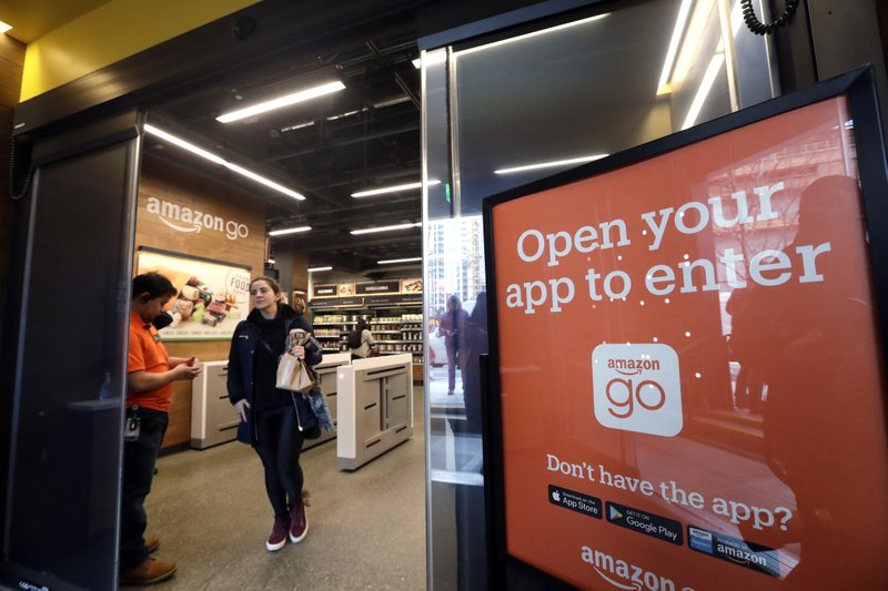 FILE- In this Jan. 22, 2018, file photo, a shopper departs an Amazon Go store in Seattle. Get ready to say good riddance to the checkout line. (AP Photo/Elaine Thompson, File)