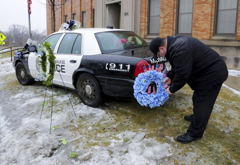 Timothy Nelson, of Oak Creek, Wis., places small flags in a bouquet near a squad car adorned with flowers as a memorial for fallen Milwaukee Police Officer Matthew Rittner at the Neighborhood Task Force police building in Milwaukee on Thursday, Feb. (Mike De Sisti/Milwaukee Journal-Sentinel via AP)