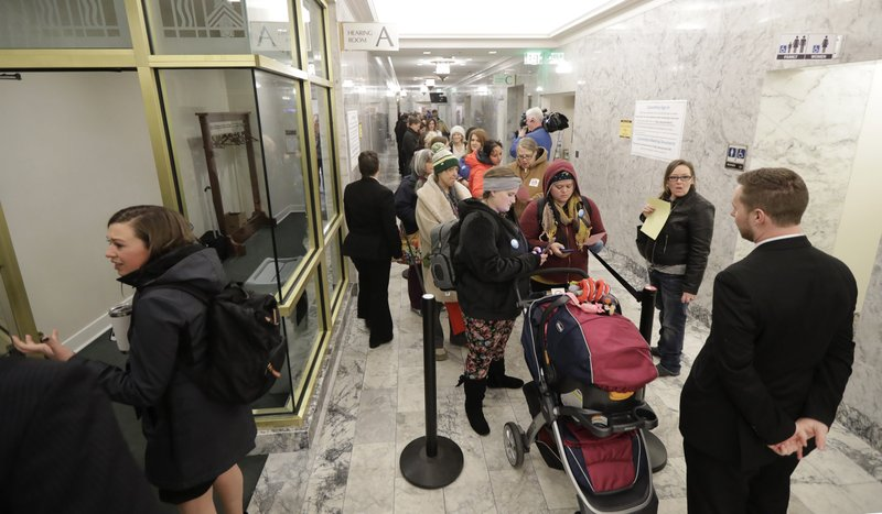 People line up in a hallway, Friday, Feb. 8, 2019, before a public hearing before the House Health Care & Wellness Committee at the Capitol in Olympia, Wash. (AP Photo/Ted S. Warren)