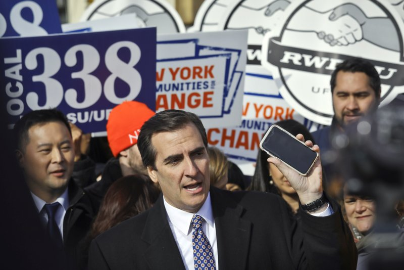 FILE - This Nov. 14, 2018 file photo shows New York State Sen. Michael Gianaris, center, as he calls on supporters to remove the Amazon app from their phones and boycott the company, as he address a coalition rally and press conference, in New York. (AP Photo/Bebeto Matthews, File)