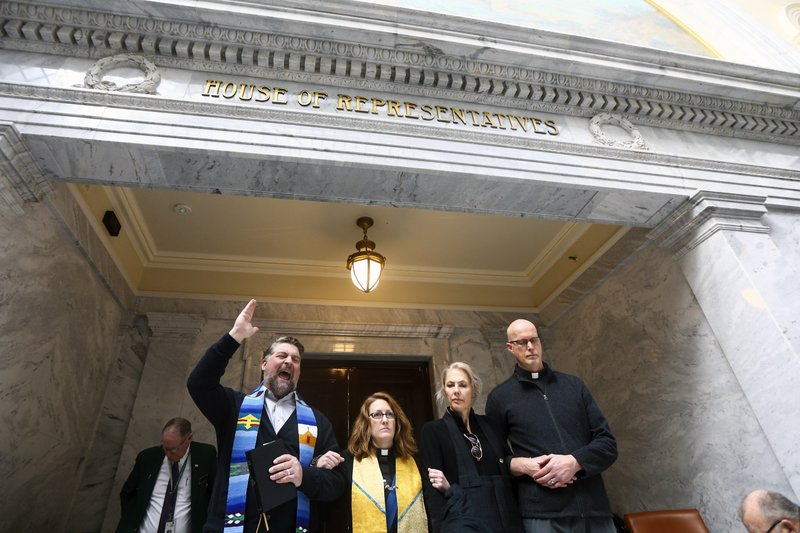 Rev. Curtis Price, left to right, Rev. Monica Dobbins, Anna Zumwalt, and Rev, David Nichols stand with locked arms in front of the House Chambers at the Capitol in Salt Lake City on Friday, Feb. (Silas Walker/The Deseret News via AP)