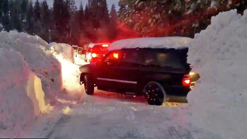This Wednesday, Feb. 6, 2019 photo from video by Joel Keeler shows vehicles driving through canyons plowed through snow drifts that overshadow them at snowed-in Montecito Sequoia Lodge in Kings Canyon National Park in California's Sierra Nevada. (Joel Keeler via AP)