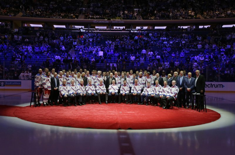 The current New York Rangers hockey team poses for a photograph with the 1994 team to acknowledge the 25th anniversary of the 1994 New York Rangers winning the Stanley Cup. (AP Photo/Frank Franklin II)