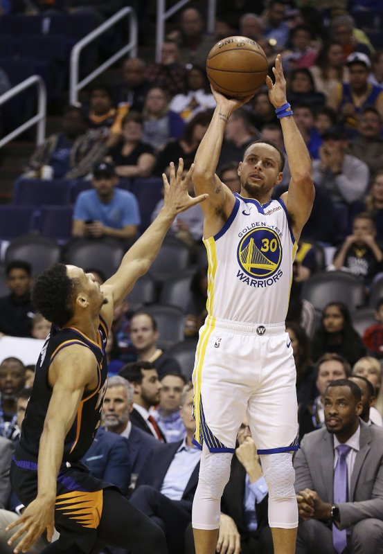 Golden State Warriors guard Stephen Curry (30) shoots over Phoenix Suns guard Elie Okobo during the first half of an NBA basketball game Friday, Feb. (AP Photo/Ross D. Franklin)