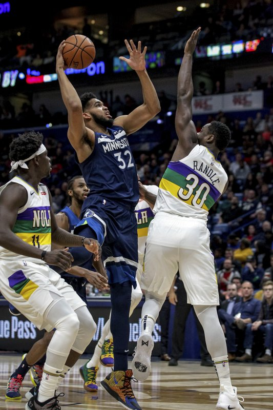 Minnesota Timberwolves center Karl-Anthony Towns (32) shoots between New Orleans Pelicans guard Jrue Holiday (11) and center Julius Randle (30) during the first half of an NBA basketball game in New Orleans, Friday, Feb. (AP Photo/Scott Threlkeld)