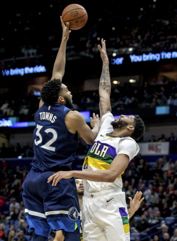 Minnesota Timberwolves center Karl-Anthony Towns (32) shoots over New Orleans Pelicans forward Anthony Davis (23) during the first half of an NBA basketball game in New Orleans, Friday, Feb. (AP Photo/Scott Threlkeld)