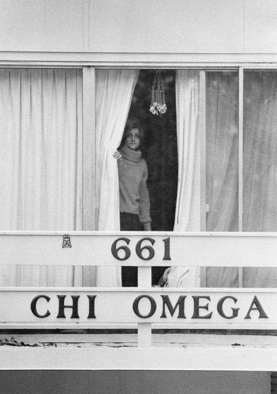 FILE - In this Jan. 15, 1978 file photo, an unidentified woman peers through drapes on the second story balcony of the Chi Omega sorority house at Florida State University in Tallahassee, Fla. (AP Photo/Mark Foley)