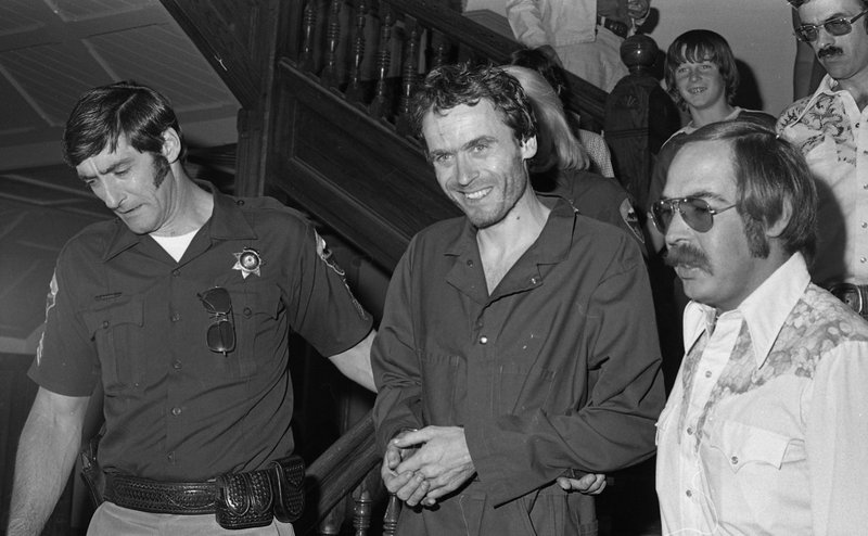 FILE - In this 1977 file photo, serial killer Ted Bundy, center, is escorted out of court at the Pitkin County courthouse, Aspen, Colo. (Ross Dolan/Glenwood Springs Post Independent via AP)