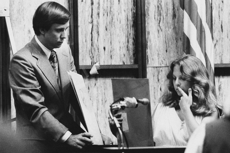 FILE - In this July 18, 1979 file photo, Nita Jane Neary, right, looks at drawing in court as prosecution attorney Larry Simpson holds additional prints during the murder trial of Ted Bundy in Miami, Fla. (AP Photo/Pool)