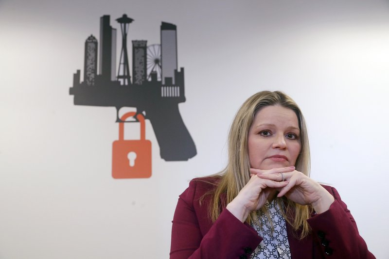 In this Thursday, Feb. 7, 2019 photo, Kimberly Wyatt, a King County senior deputy prosecutor who is part of a regional unit that enforces Extreme Risk Protection Orders (ERPO), poses for a portrait near the logo for the unit in Seattle. (AP Photo/Elaine Thompson)