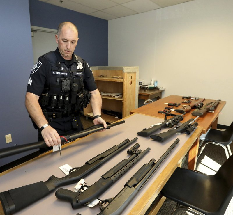In this May 23, 2018, photo, Seattle Police Crisis Response Team Sgt. Eric Pisconski displays guns seized from people deemed to be a danger to themselves or others. (Greg Gilbert/The Seattle Times via AP)