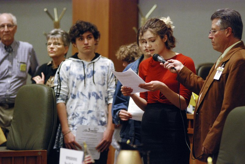 In this Monday, Feb. 4, 2019, photo, high school student Sophia Lussiez, 17, of Santa Fe, N.M., second from right, testifies in support of proposals for new gun safety regulations in the state, in Santa Fe, N. (AP Photo/Morgan Lee)