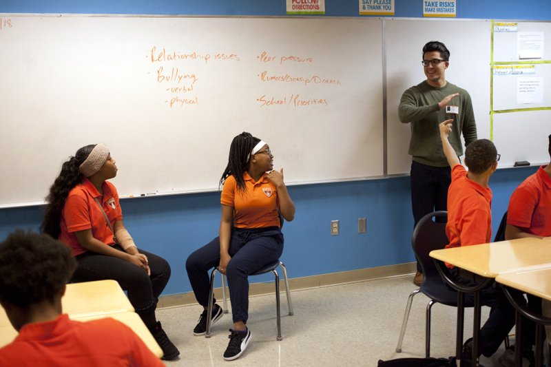 In this Nov. 15, 2018 photo, Marshall Motsenbocker, standing right, a researcher at the University of Texas Southwestern Medical Center, leads a Youth Aware of Mental Health session at Uplift Hampton Preparatory School in Dallas. (AP Photo/Benny Snyder)
