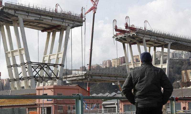 A man looks the Morandi bridge in Genoa, Italy, Saturday, Feb. 9, 2019. Workers taking apart the remains of a bridge which collapsed in Aug. (AP Photo/Antonio Calanni)