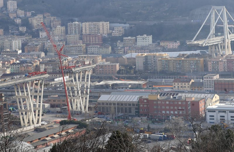 Cranes lower a section of the Morandi bridge in Genoa, Italy, Saturday, Feb. 9, 2019. Workers taking apart the remains of a bridge which collapsed in Aug. (AP Photo/Antonio Calanni)